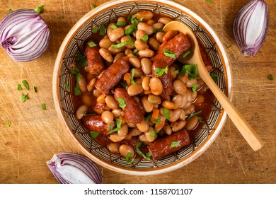 Beans stew wit pork sausages and tomato sauce on wooden table with purple onion - top view