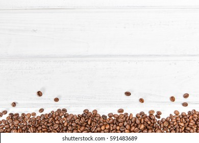 Ð¡offee beans stripe on white wood background.  Copyspace for text.