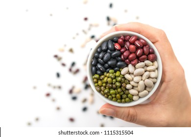 Beans in a white cup on a woman's hands with isolated a white background. Top view.