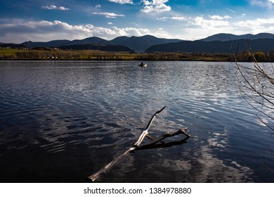 Bear Creek Lake with rocky mountains and  blue sky with white clouds in background, ripples on lake surface