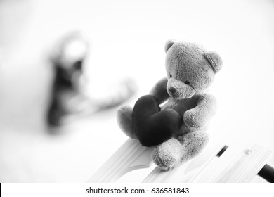 bear doll and red heart with black and white tone