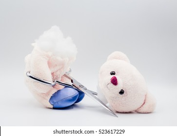 bear doll use scissors to cut himself a teddy bear : Suicide bear.Bear with his head cut off isolated on white background