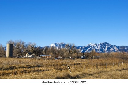Bear and Green Peaks and the Flatirons tower above a peaceful farm on the Colorado prairie near Boulder.