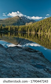 Bear lake in rocky mountain national park colorado early morning reflection. Reflective photo of glassy smooth lake and the surrounding mountains early in the morning. Green trees and blue skies