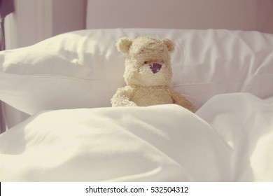 Bear is  laying in bed. Idea for sick or lazy in bed in bedroom.