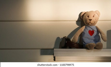 a bear little doll sitting on the white shelve and white wooden wall, a bear wear blue stripped shirt with red heart and brown skin, the watch beside. The light is low and the shadow reflect on the wa