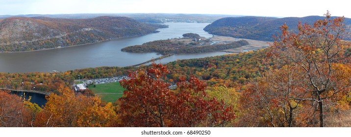Bear Mountain Autumn panorama aerial view with colorful trees in forest, bridge over Hudson River in New York State.