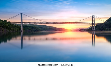 Bear Mountain Bridge at sunrise (long exposure). Bear Mountain Bridge is a toll suspension bridge in New York State, carrying U.S. Highways 202 and 6 across the Hudson River