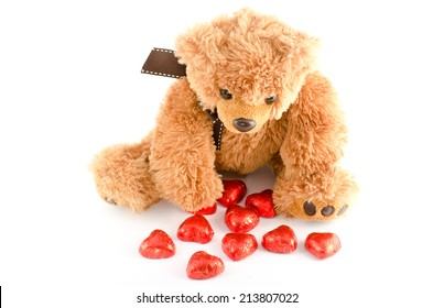 Bear with red chocolate hearts isolated on white