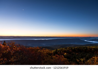 Bear rocks overlook during sunrise, dawn, moon in autumn with rocky landscape in Dolly Sods, West Virginia with orange foliage trees, blue, yellow sky, layered mountains, hills