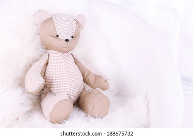 Bear toy on armchair in room