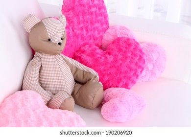 Bear toy with pillows on sofa