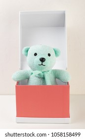 bear toy in a red cardboard box