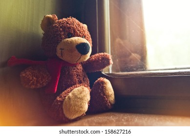 Bear toy sitting by the window