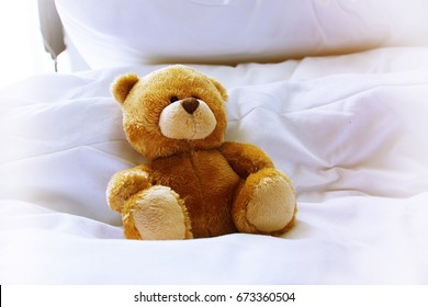 A bear wears towel on her head is on her bed on white pillow and white duvet