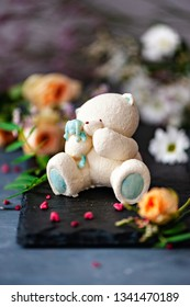 BEAR of white chocolate on a dark Board on a background of flowers. Romance. Selective focus.