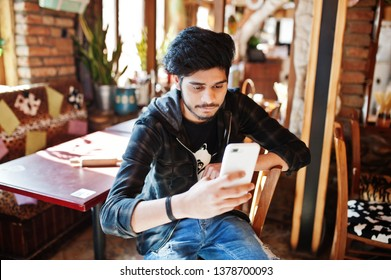 Beard asian man in casual wear sitting indoor cafe and look at his phone.