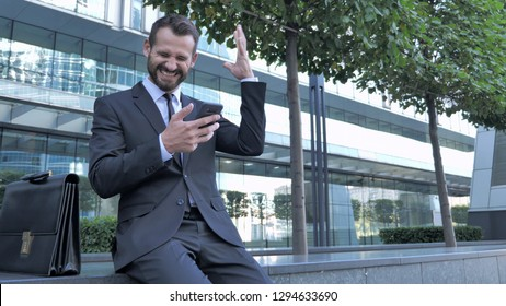 Beard Businessman Excited for Success while Using Smartphone