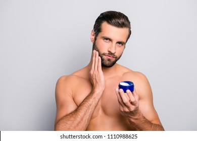 Beard care concept. Portrait of sexy attractive with perfect body muscular virile masculine with ideal haircut applying moisturizing cream on cheeks isolated on gray background copy-space