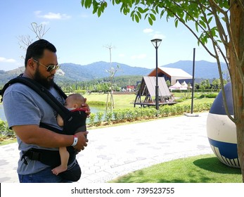 Beard father with sunglasses holding daughter in babywearing outdoor.