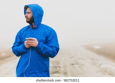 Beard man dressed in blue rain coat standing in the middle of nowhere checking his phone. Fog.
