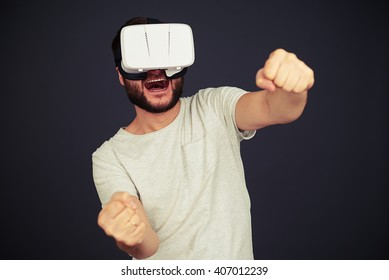 Beard man driving in virtual reality wearing hi-tech VR headset, on black background