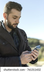 Beard man touching smartphone sending message or looking notifications in outdoors park