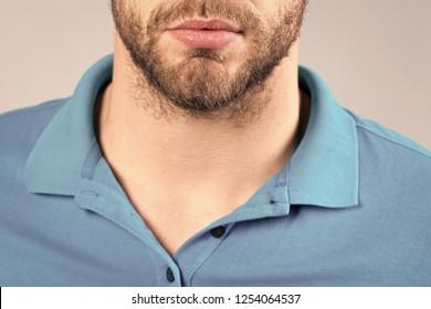 Beard, mustache design in barber salon. Bearded chin, mouth, and blue tshirt collar. Barbershop, barber salon. Skin care, grooming beauty