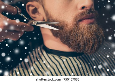 Beard styling and cut. Close up cropped photo of a styling of a red beard. So trendy and stylish! Advertising and barber shop concept, snowflakes background