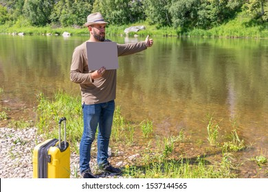 bearded 23 year guy with sign in hands, empty place for text. young traveler man with a suitcase stands on banks of river. catches transport thumbs up. Concept of travel, journey, holidays, vacation.