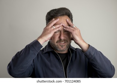 Bearded adult male looking in pain with hands on head