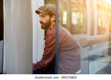 Bearded adult male with trendy look is sitting in the fresh air on a bus stop and waiting for a taxi, fashionable hipster guy with stylish retro hat on the head is taking break between walk outdoors