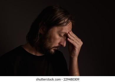 Bearded adult man with migraine headache, low key portrait