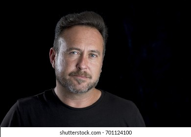 Bearded adult white man's face over a black background with copy space
