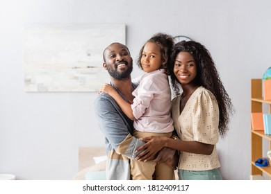 bearded african american man holding daughter near mother hugging them and looking at camera