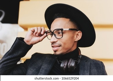Bearded african man with short haircut touching his glasses. Close-up outdoor photo of black boy in hat and music headphones.