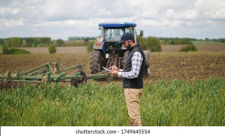 Bearded agronomist wearing a cap uses a specialized app on a digital tablet PC on the background of working tractor with a cultivator in the field - Shutterstock ID 1749645554