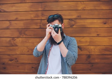 Bearded amateur with spectacles on head making cool photos on vintage camera with modern lens standing against wooden promotional background for advertising text.Male photographer taking pictures