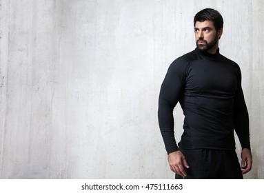 Bearded athlete black blank T-shirt with long sleeves standing on cement wall background with free space on the left