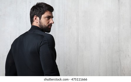Bearded athlete black blank T-shirt with long sleeves is back on the cement wall background with free space on the right