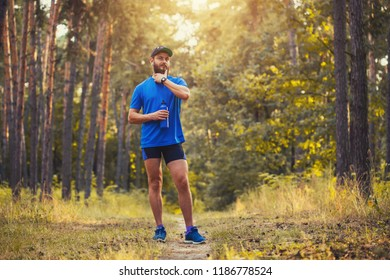 A bearded athlete prepares for a morning run along a picturesque forest path. healthy lifestyle concept