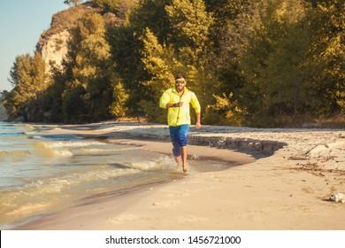 bearded athlete runs along the sandy beach. active lifestyle