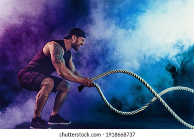 Bearded athletic looking bodybulder work out with battle rope on dark studio background with smoke. Strength and motivation.