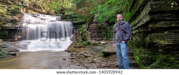 Bearded Backpacker wearing jeans near a waterfall at Buttermilk