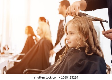 Bearded barber makes curls on hair of beautiful little girl with hair curler. Female stylist makes stylish hairstyle to little girl.