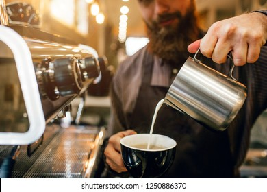 Bearded barista pours milk into cup with coffee. He does it very accurate. Guy works at coffee machine.