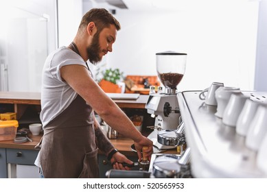 bearded barista tamping ground coffee