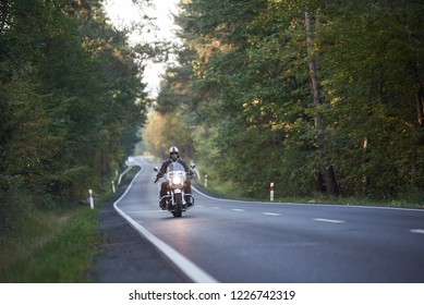 Bearded biker in sunglasses, helmet and black leather clothing riding modern powerful high-speed motorcycle along asphalt road winding among tall green trees.