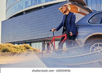 Bearded blond male with long hair holds fixed bicycle near the car with open trunk.