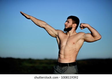 Bearded body builder poses with naked chest on a green field